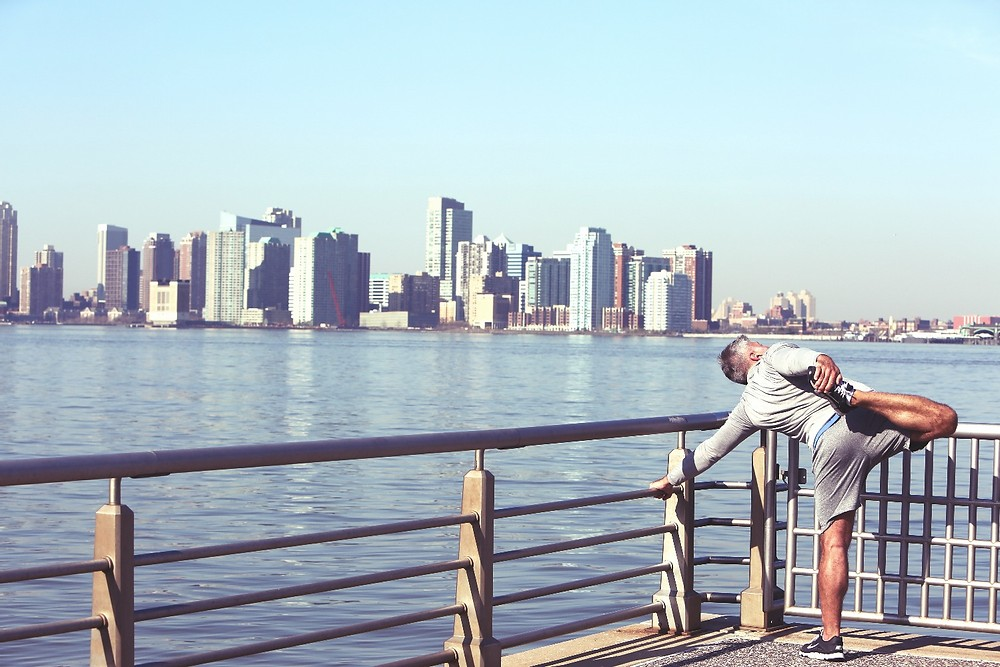 Man stretching with Hudson River and NYC in background